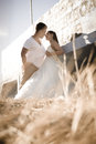 Young beautiful couple flirting outdoors in long grass against wall Royalty Free Stock Images