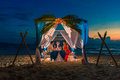 Young beautiful couple have a romantic dinner at sunset on tropical beach honeymoon Royalty Free Stock Photo
