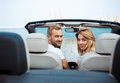 Young beautiful couple holding map, sitting in car near seacoast Royalty Free Stock Photo