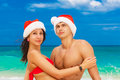 Young beautiful couple in love having fun in the waves dressed i red santa claus hats christmas and new year on tropical Royalty Free Stock Photos