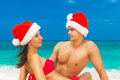 Young beautiful couple in love having fun in the waves dressed i red santa claus hats christmas and new year on tropical Royalty Free Stock Photography