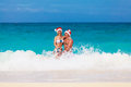 Young beautiful couple in love having fun in the waves dressed i red santa claus hats christmas on tropical coast Royalty Free Stock Photography