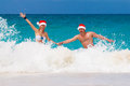 Young beautiful couple in love having fun in the waves dressed i red santa claus hats christmas on tropical coast Royalty Free Stock Photo