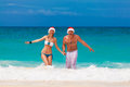 Young beautiful couple in love having fun in the waves dressed i red santa claus hats christmas on tropical coast Stock Photos