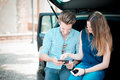 Young beautiful couple lovers using tablet in the car travel Stock Image
