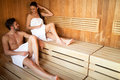 Young and beautiful couple relaxing in a sauna with towel coveri Royalty Free Stock Photo