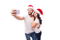 Young beautiful couple in santa hats in love taking romantic self portrait christmas selfie photo together with mobile phone Royalty Free Stock Images