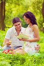 Young beautiful couple sitting on grass in the park smiling and Royalty Free Stock Photo