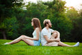 Young beautiful couple smiling, sitting on grass in park. Outdoor background. Royalty Free Stock Photo