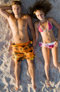Young beautiful couple sunbathing on the beach Stock Photos