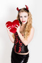 Young and beautiful curly girl with red horns looks like pretty Devil, holding a heart pillow Royalty Free Stock Photo