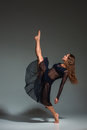Young beautiful dancer in black dress posing on a dark gray studio background Royalty Free Stock Photo