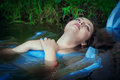 Young beautiful drowned woman in blue dress lying in the water outdoor Stock Photography