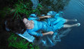 Young beautiful drowned woman lying in the water blue dress Stock Photos