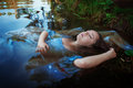Young beautiful drowned woman lying in the water blue dress outdoor Stock Photo