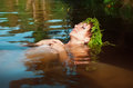 Young beautiful drowned woman lying in the water with fern wreath Royalty Free Stock Images