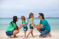 Young beautiful family with two daughters having kids walking at tropical beach Royalty Free Stock Images