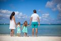 Young beautiful family with two kids walking at tropical beach Royalty Free Stock Photo