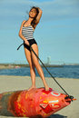 Young beautiful fashion model in onepiece stripped swimsuit posing at the beach with the bouy Stock Photography