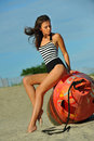 Young beautiful fashion model in onepiece stripped swimsuit posing at the beach with the bouy Stock Photo
