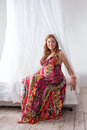 Young beautiful fashion pregnant woman in colorful dress sitting on a bed with canopy white background Royalty Free Stock Photos