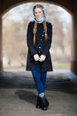 Young beautiful fashionable redhead woman with braids hairdo in blue white headcraft stylish denim black trench jacket posing outd Royalty Free Stock Photo