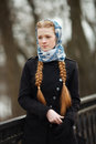 Young beautiful fashionable redhead woman with braids hairdo in blue white headcraft stylish denim black trench jacket posing on s Royalty Free Stock Photo