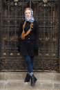 Young beautiful fashionable redhead woman with braids hairdo in blue white headcraft stylish denim black trench jacket posing wrou Royalty Free Stock Photo