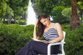 Young beautiful female reading book in park romantic woman sitting on chair behind fountain Royalty Free Stock Photo