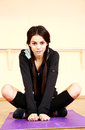 Young beautiful fit woman sitting on the yoga mat at gym Stock Photography