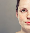 Young beautiful freckles woman half face portrait with healthy skin Royalty Free Stock Photo