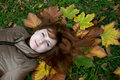 Young beautiful ginger lying on the autumn leaves Royalty Free Stock Photo