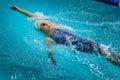 Young beautiful girl athlete swims backstroke Royalty Free Stock Photo