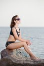Young beautiful girl in bikini sits on stone near sea with bottle of water Royalty Free Stock Photo