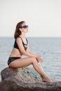 Young beautiful girl in bikini sits on stone near sea with bottle of water Royalty Free Stock Photo
