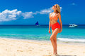 Young beautiful girl in bikini is standing on the beach. Blue tr Royalty Free Stock Photo