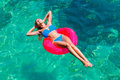 Young beautiful girl in bikini swims in a tropical sea on a rubb Royalty Free Stock Photo