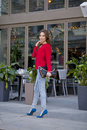 Young beautiful girl in blue jeans and red shirt on the backgrou Royalty Free Stock Photo