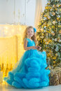 Young beautiful girl in blue white elegant evening dress sitting on floor near christmas tree and presents on a new year Royalty Free Stock Photo