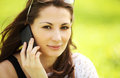 Young beautiful girl in city park speaks by mobile phon image of phone Royalty Free Stock Image