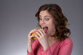 Young beautiful girl disdainfully holding a junk food from fast Royalty Free Stock Photo
