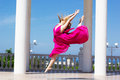 Young beautiful girl doing gymnastic outdoors in pink dress jumps Royalty Free Stock Photography