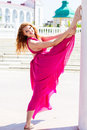 Young beautiful girl doing gymnastic outdoors in pink dress jumps Stock Photography
