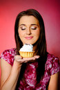Young beautiful girl eating small sweet cake Stock Photos