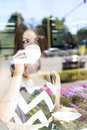 Young beautiful girl in glass showcase a cafe, sunny day, holding  mug of tea Royalty Free Stock Photo