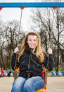 Young beautiful girl having fun riding a chain-swing in the park Royalty Free Stock Photo