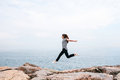 Young beautiful girl jumping upwards portraying a flight against the background of the sea and sky. The concept of Royalty Free Stock Photo
