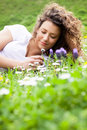 Young beautiful girl laying on the flowers field summer concept outdoor portrait Royalty Free Stock Images