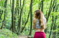 Young beautiful girl with long hair european appearance poses during a walk in the park among the trees and vegetation Royalty Free Stock Image