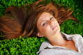 Young beautiful girl lying on green grass Stock Photo